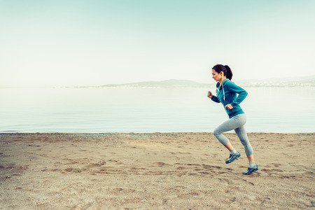 Girl running on sand beach near the sea in summer in the morning. Concept of sport and healthy lifestyle. Space for text in the left part of image Standard-Bild