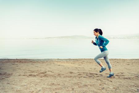 stile di vita: Ragazza che funziona sulla spiaggia di sabbia vicino al mare in estate al mattino. Concetto di sport e stile di vita sano. Spazio per il testo nella parte sinistra dell'immagine