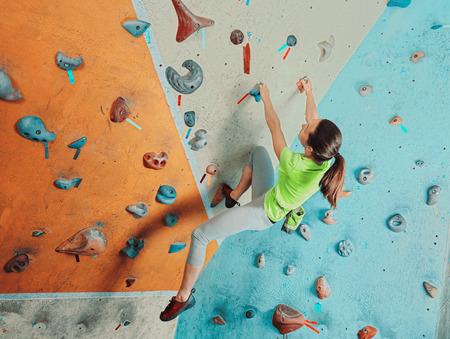 Mooie sportieve jonge vrouw klimmen op praktische muur in de sportschool, boulderen