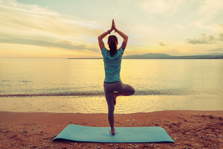 female pose: Young woman doing yoga exercise in pose of tree on beach at sunset in summer, rear view Stock Photo
