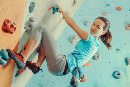rock wall: Young woman exercising in a climbing gym, looking at camera
