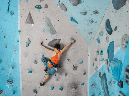 Boy wearing in safety equipment climbing on artificial boulders in gym