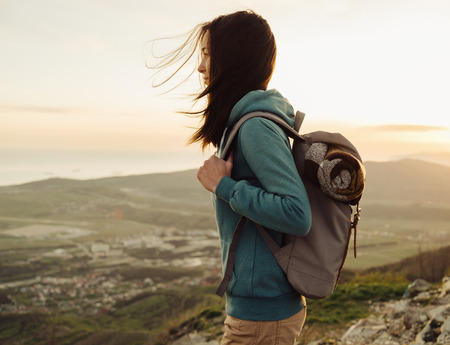 Hiker young woman with backpack standing on peak of mountain in summer at sunset