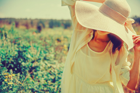 instagram: Fashionable young woman in a hat with wide brim resting in summer park. Image with instagram color effect