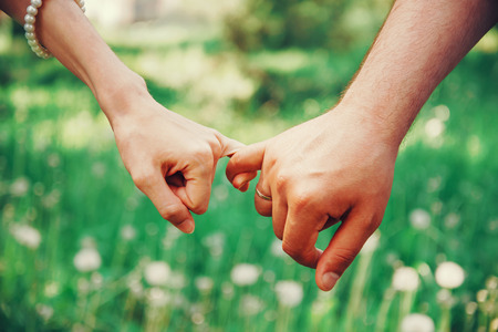 couple married: Married young loving couple holding hands each other in summer park, view of hands