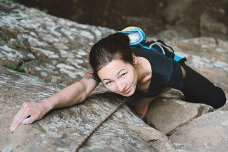 rock climb: Beautiful young woman in safety equipment climbing on stone rock, top view Stock Photo