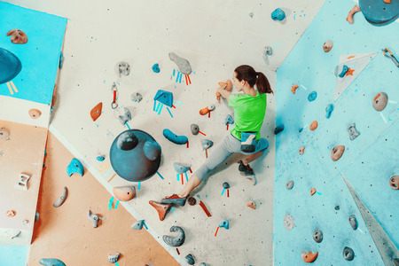 magnesia: Sporty young woman exercising in a colorful climbing gym