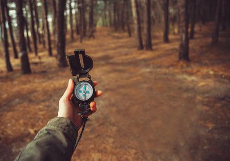 Caminhante da mulher procura o sentido com um compasso na floresta. Vista de mãos. Ponto de vista tiro. Espaço para o texto na direita esquerda da imagem