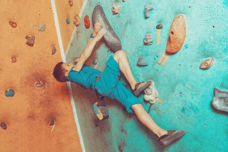 free climber: Free climber little boy climbing artificial boulder on practical wall in colorful gym Stock Photo