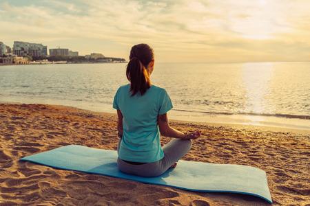 Jonge vrouw mediteren in pose van lotus op zandstrand in de buurt van de zee bij zonsondergang in de zomer