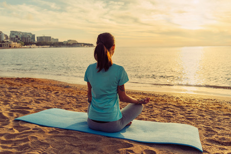 Young woman meditating in pose of lotus on sand beach near the sea at sunset in summer 免版税图像