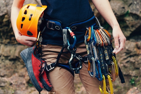 Woman standing with climbing equipment and helmet outdoor, front view. Face is not visible