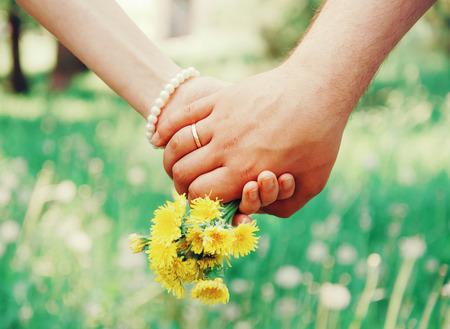 parejas de amor: Pareja joven amante de la mano unos a otros con el ramo de dientes de león amarillo en el parque de verano, vista de manos