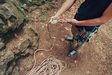 safety harness: Climber woman wearing in safety harness with equipment holding rope and preparing to climb, top view