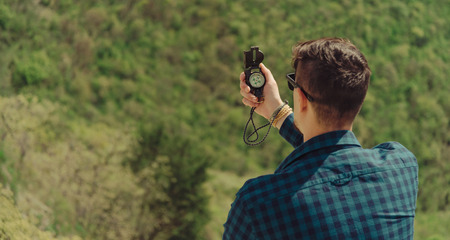 man searching: Hiker young man searching direction with a compass in summer Stock Photo