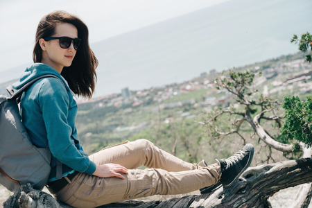 woman outdoor: Beautiful traveler young woman resting on tree above the sea in summer