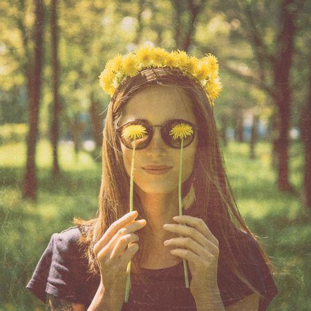 Smiling beautiful girl in wreath of yellow dandelions closed her eyes with dandelions in summer park, concept of happiness and summer mood. Image with old textured effect