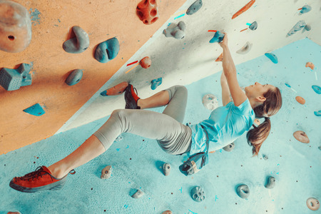 climb: Sporty young woman training in a colorful climbing gym. Free climber girl climbing up indoor