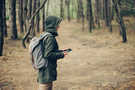 woman hiking: Hiker young woman working on digital tablet PC in the forest Stock Photo