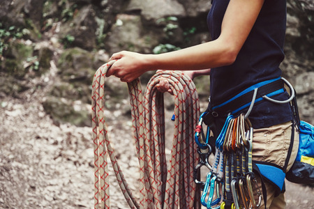 Climber woman wearing in safety harness with equipment holding rope and preparing to climb