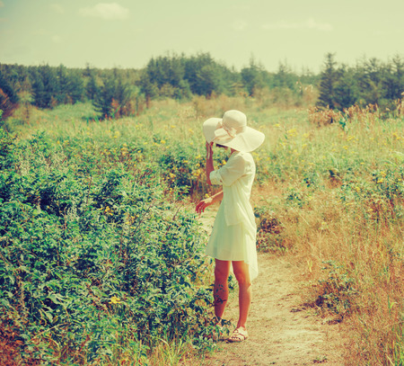brim: Beautiful woman in a hat with wide brim and dress walking outdoor in summer.