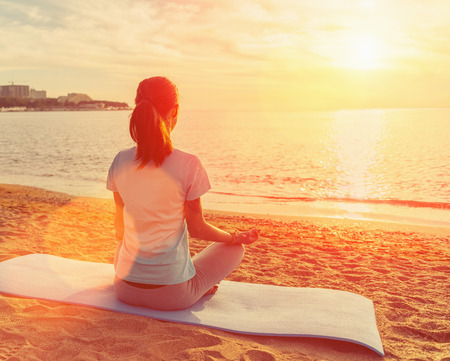 Young woman meditating in pose of lotus on sand beach near the sea at sunset in summer. Image with sunlight effect Standard-Bild