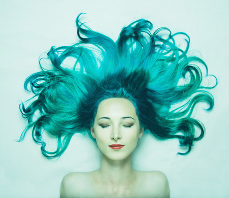 Portrait of smiling beautiful young woman with closed eyes and long hair of turquoise color, top view. Image of mermaid