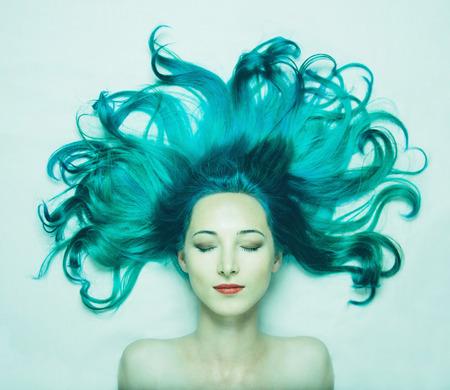 Portret van lachende mooie jonge vrouw met gesloten ogen en lang haar van turquoise kleur, bovenaanzicht. Afbeelding van zeemeermin Stockfoto
