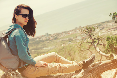 autumn young: Beautiful traveler young woman resting on tree above the sea in summer. Image with sunlight effect