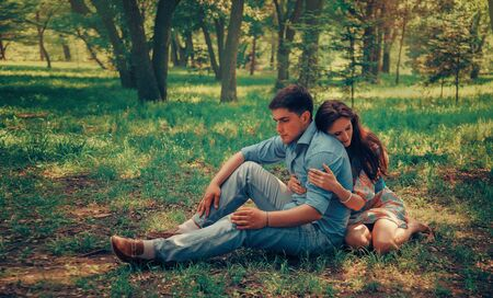man woman hugging: Young loving couple resting on summer meadow in the park, woman hugging a man.