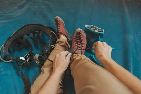 point of view: Sporty woman putting on climbing shoes and preparing to climb, point of view shot Stock Photo
