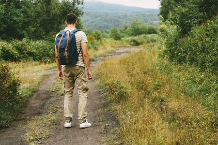 Hiker young man with backpack walking on footpath in summer forest