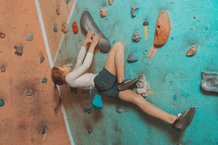 magnesia: Climber little sporty girl exercises on artificial boulders wall indoor