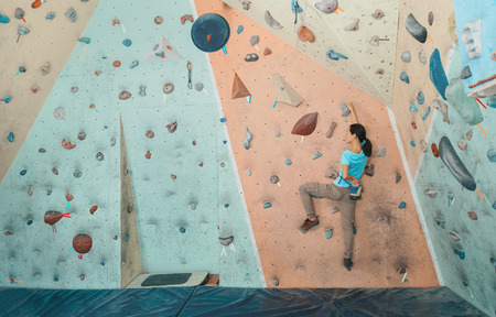 Free climber young woman exercises to climbing artificial boulder indoor, bouldering. Climber putting her hand in the bag of powder magnesia Standard-Bild