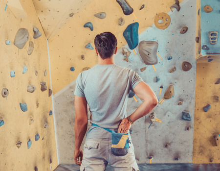 sportsmen: Sporty young man standing in front of a practical climbing wall indoor and preparing to climb. Climber putting his hand in the bag of powder magnesia