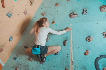poses: Climber little girl exercises in gym. Climber girl sitting on artificial boulders in pose of frog