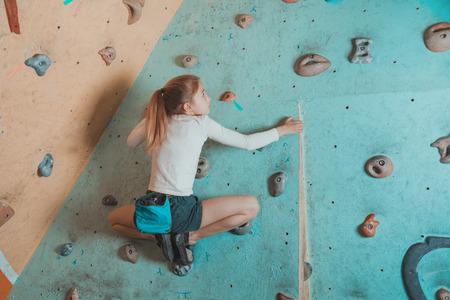niño trepando: Escalador pequeños ejercicios chica en el gimnasio. Muchacha del escalador que se sienta en rocas artificiales en pose de rana Foto de archivo