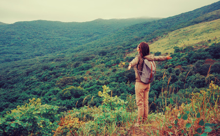 Freedom happy traveler woman standing with raised arms and enjoying a beautiful nature. Image with instagram color effect. Stock Photo