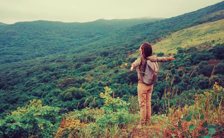 旅遊: 自由快樂的旅行者的女人站在雙臂抬起,並享受美麗的自然風光。圖像的Instagram的色彩效果