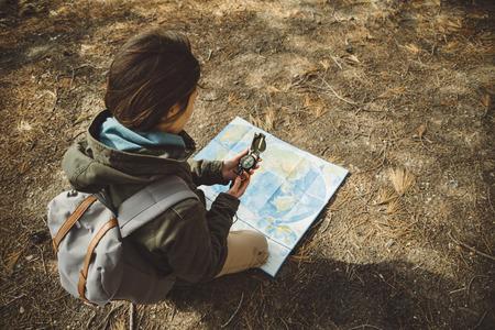 Traveler jonge vrouw met rugzak op zoek richting met een kompas op de achtergrond van de kaart in het bos. Focus op kompas Stockfoto