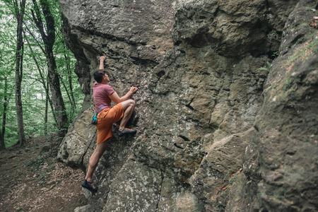 bouldering: Libero scalatore uomo iniziando a arrampicata su roccia di pietra all'aperto in estate, bouldering