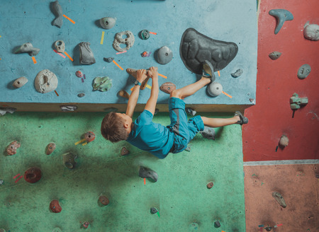 magnesia: Climber boy exercises on artificial boulders wall in gym