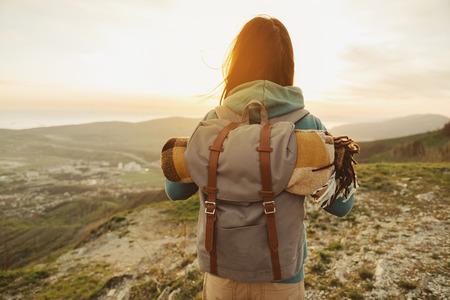 Turysta kobieta z plecak i śpiwór spacery w górach latem o zachodzie słońca