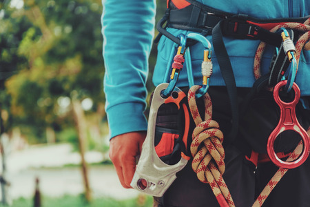safety harness: Rock climber wearing safety harness and climbing equipment outdoor, close-up image Stock Photo