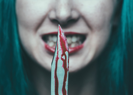 macabre: Spooky dangerous woman with knife in blood. Halloween or horror theme Stock Photo