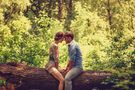 Young loving couple sitting on fallen trunk tree in summer park, tender scene Standard-Bild