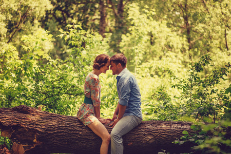 loving couple: Young loving couple sitting on fallen trunk tree in summer park, tender scene Stock Photo
