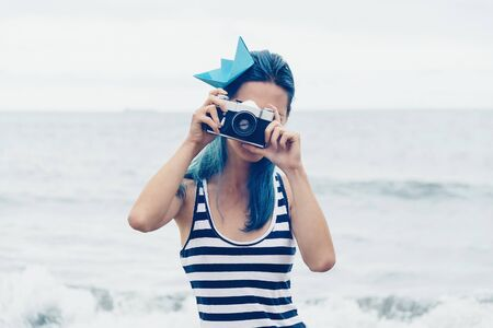filters: Beautiful young woman takes a photograph with old photo camera on beach in summer Stock Photo