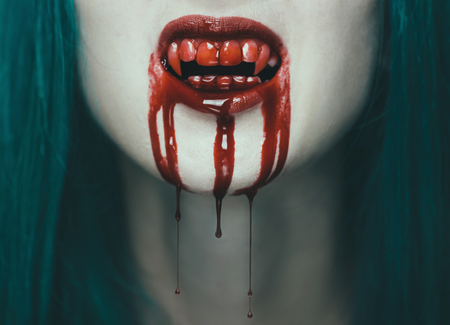 horror: Scary vampire woman, close-up of mouth with teeth in blood. Halloween or horror theme
