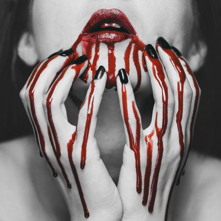 젊은여자가 그녀의 얼굴에 혈액을 만지고. 할로윈과 공포 테마입니다. 빨간색 요소가있는 흑백 이미지